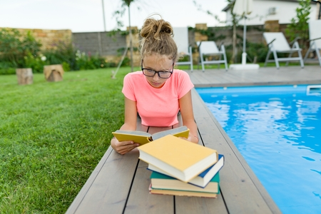Teenage girl in glasses reads a book, background swimming pool, lawn near the house. School, education, knowledge, adolescents