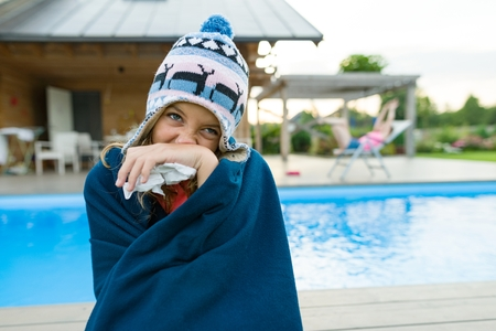 Flu, colds in the summer. Girl in a knitted hat with plaid with handkerchief sneezes, wipes her nose. Background nature, pool, girlfriend in chaise longue