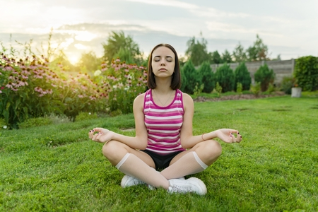 Young teenage girl practicing yoga, meditating on a summer sunset background, on green grass, lawn near the house