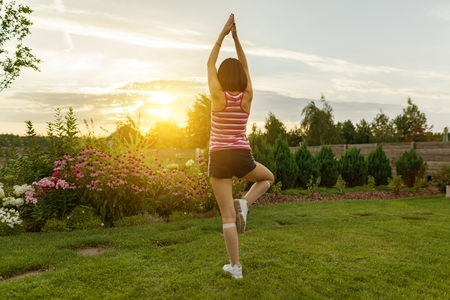 Young girl practicing yoga, meditating on a summer sunset background, on green grass, lawn near the house