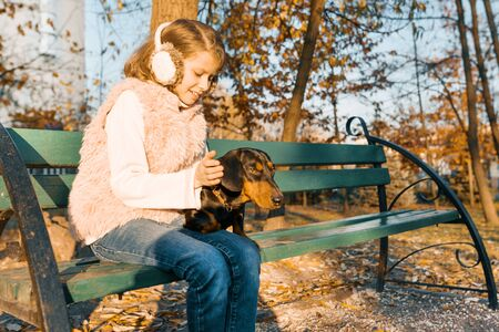 Smiling little owner of a dachshund dog sitting on bench in the autumn park, girl with love hugging dog at the golden hour.