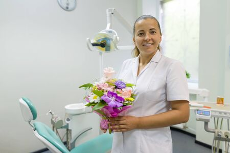 Female dentist smiling, with a bouquet of flowers, in dental office. National dentists day 版權商用圖片