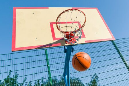 Street basketball, close-up of basketball ring and ball flying into the basket. Archivio Fotografico - 134737777