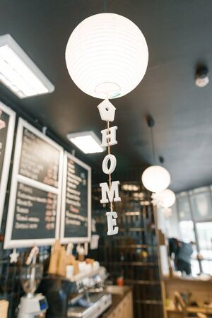 Modern coffee shop, interior, bar counter, focus on white round paper lamp and the word home in wooden letters. Home cafe concept.