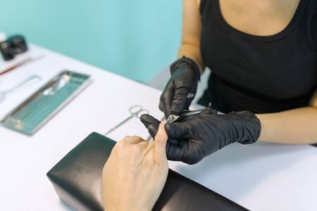 Close-up process of professional manicure, hands of manicurist and female client, instruments.