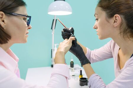 Nail and hand care in beauty salon. Young woman doing professional manicure.
