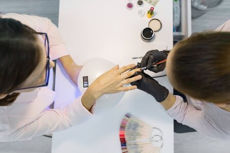 Top view, woman manicurist doing manicure, painting nails, using ultraviolet lamp for fixing gel nail polish. Nail and hand care in beauty salon.