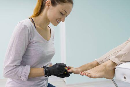 Closeup pedicure process. Young woman getting professional pedicure, beauty salon, nail care