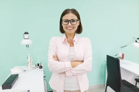 Portrait of mature woman owner of beauty salon for nail care and hands with arms crossed, background beauty salon.