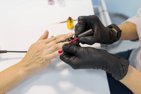 Colored manicure, nail painting. Woman manicurist doing professional manicure, using color gel polish, nail and hand care in beauty salon Zdjęcie Seryjne