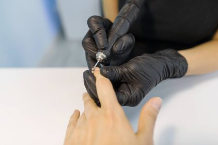Closeup process of professional manicure. Manicurist woman hands in black gloves making manicure using professional tools. Nail and hand care in beauty salon.