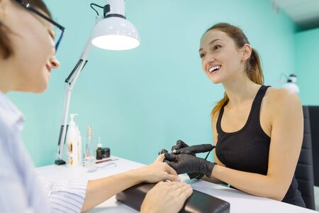 Woman in nail salon receiving manicure by manicurist, closeup manicure process. Nail and hand care in beauty salon
