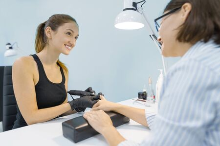 Young smiling woman beautician in beauty nail salon doing manicure with professional tools, nail and hand care.