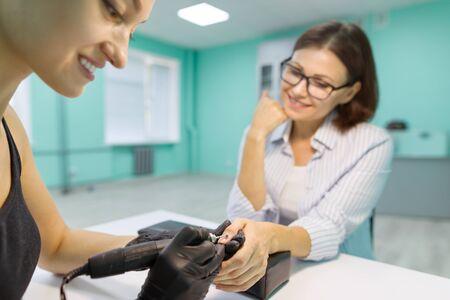 Closeup manicure process. Young woman getting professional manicure, beauty salon, nail care