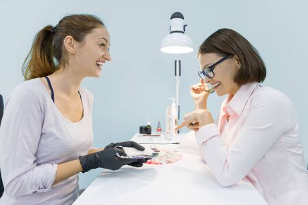 Young smiling beautician woman manicurist talking to a female client, does manicure, woman choosing a color of nail polish. Zdjęcie Seryjne