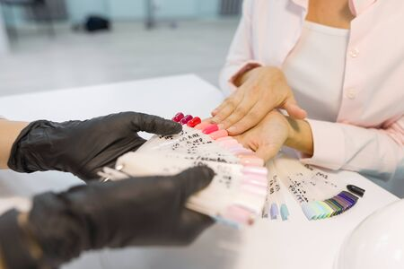 Close-up of female client choosing nail-polish color for her nails. Nail and hand care in beauty salon.