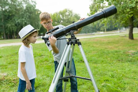 Children teenagers in the park looking through a telescope.
