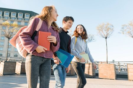 Outdoor portrait of teenage students with backpacks walking and talking. City background, golden hour.