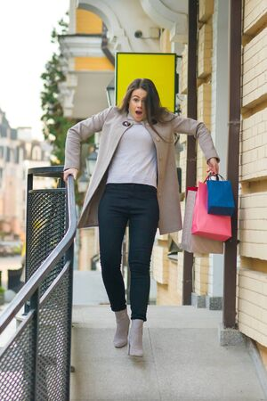 Young woman comes out of the store and slipped. Banque d'images