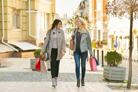 Dos jóvenes mujeres sonrientes en una calle de la ciudad con bolsas de compras, día soleado de otoño. Foto de archivo