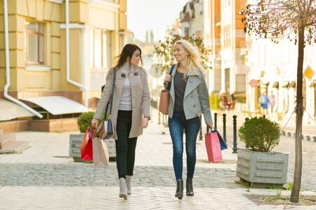 Two young smiling women on a city street with shopping bags, sunny autumn day. Reklamní fotografie