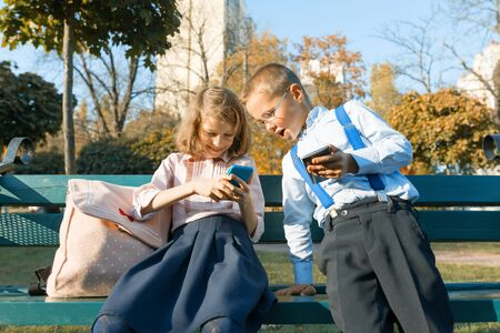 Fun children boy and girl are looking into smartphones. On a bench with school backpacks, background autumn sunny park, golden hour.