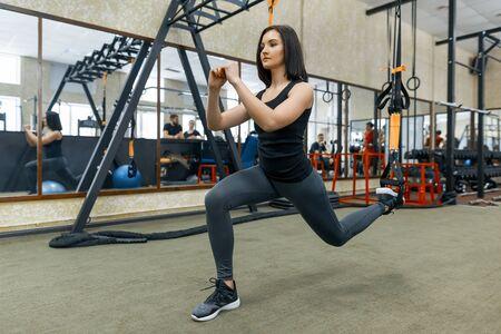 Mujer joven fitness haciendo ejercicios con el sistema de correas en el gimnasio. Deporte, fitness, entrenamiento, concepto de personas Foto de archivo