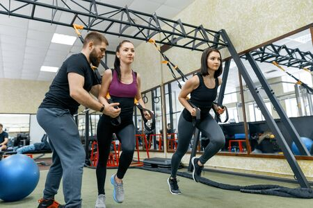 Fitness trainer coaching and helping women doing exercises on cross fit using straps system in gym. Sport, teamwork, training, people concept