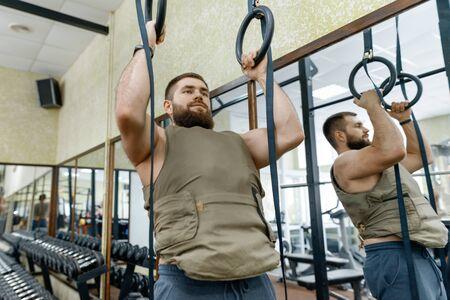 Hombre barbudo caucásico musculoso haciendo ejercicios vestido con chaleco lastrado en el gimnasio, estilo militar.