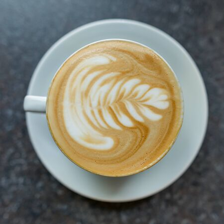 Coffee art in white cup with saucer on the gray stone surface of the table. Imagens