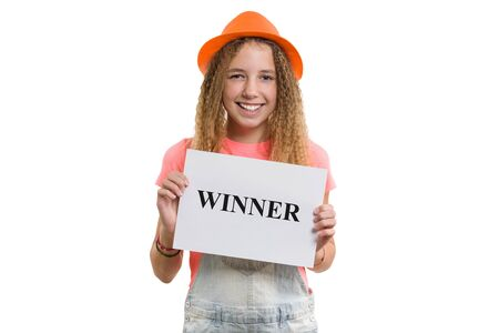 Winner text message written on white paper in hands pretty young teen girl, smiling girl in hat on isolated white background.