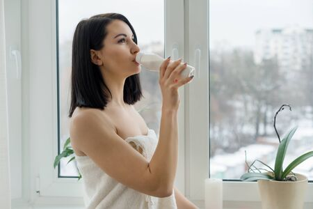Morning portrait of young woman in bath towel drinking milk drink yogurt from bottle, woman standing at home near the window, healthy food eating. Фото со стока