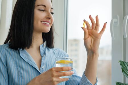 Woman takes pill with omega-3 and holding glass of fresh water with lemon. Morning picture of house, near the window. Vitamin D, E, fish oil capsules. Nutrition, healthy eating, lifestyle.
