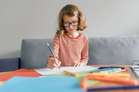Girl of 8 years sitting on sofa at home drawing writing with pencil in notebook. Child blonde with glasses studying at home.