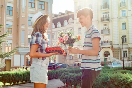 Teen boy congratulates girl with bouquet of flowers and gift, outdoor portrait couple happy youth. Banco de Imagens