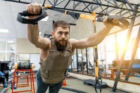 Muscular bearded man dressed in military weighted armored vest doing exercises using straps systems in the gym. Sport, training, bodybuilding and healthy lifestyle concept