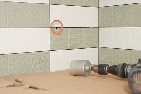 Preparatory work for the installation of an electrical outlet, building tools, tile cutter, grinder in the process of drilling tiles. Round hole in the ceramic tile.