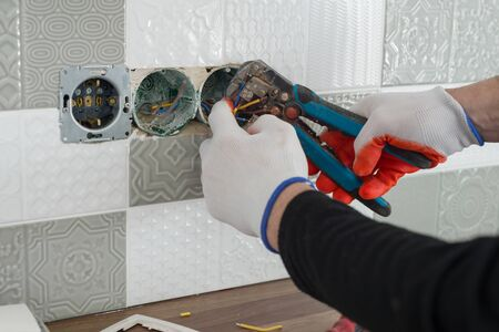 Renovation and construction in kitchen, close-up of electricians hand installing outlet on wall with ceramic tiles using professional tools.