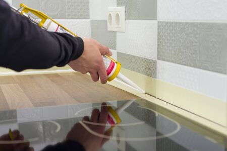 Applying silicone sealant with construction syringe. Worker fills seam between the ceramic tiles on the wall and kitchen worktop.