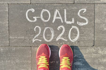 2020 goals, written on gray sidewalk with woman legs in sneakers, top view. Standard-Bild - 142230894