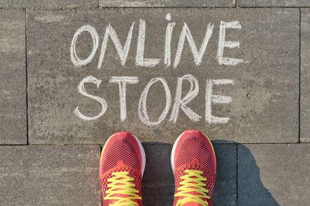 Word online store written on gray sidewalk with women legs in sneakers, top view.