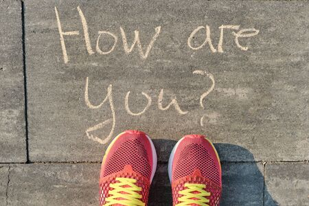 How are you, written on gray sidewalk with womens legs in sneakers, top view.