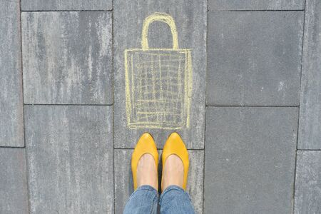 Shopping bag picture written on gray sidewalk in crayons with women legs in yellow shoes, top view