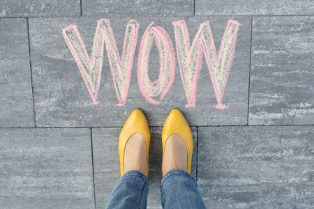 Wow written on gray sidewalk with woman legs in feet in yellow shoes, top view Stock Photo