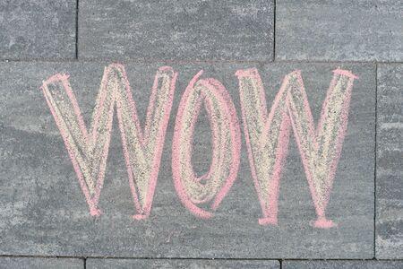 Wow written on gray sidewalk, top view.