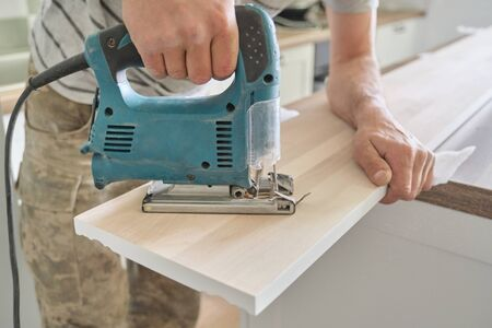 Close-up of carpenters hand using professional woodworking electric tools when working with wood. Male carving hole in wooden panel board, carpentry, woodwork, profession, people.