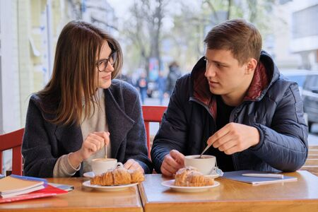 Young male and female friends students sitting in outdoor cafe, talking, drinking coffee, tea, eating croissants. On table textbooks, notebooks, city background Stock fotó