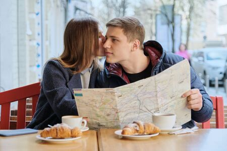 Young beautiful couple of tourists resting in outdoor cafe, reading city map, drinking coffee with croissants