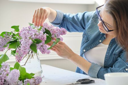 Middle-aged woman making bouquet of lilac branches, close-up female arranging flowers bunch in vase at table near the window