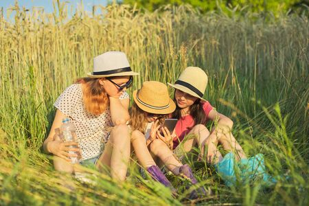 Portrait of three girls sitting and resting in grass, children talking, looking at smartphone laughing on sunny summer day, sunset in meadow 版權商用圖片